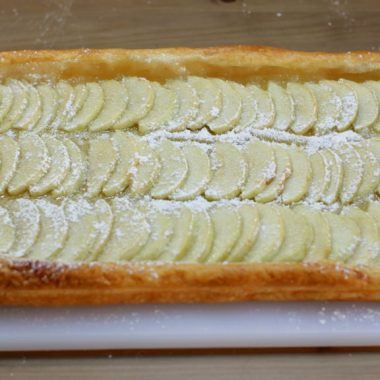 Apple tart puff pastry on a white cutting board on a wooden table
