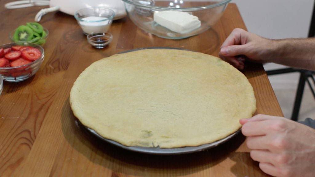 Baked sugar cookie crust in a pan on top of a wooden table.