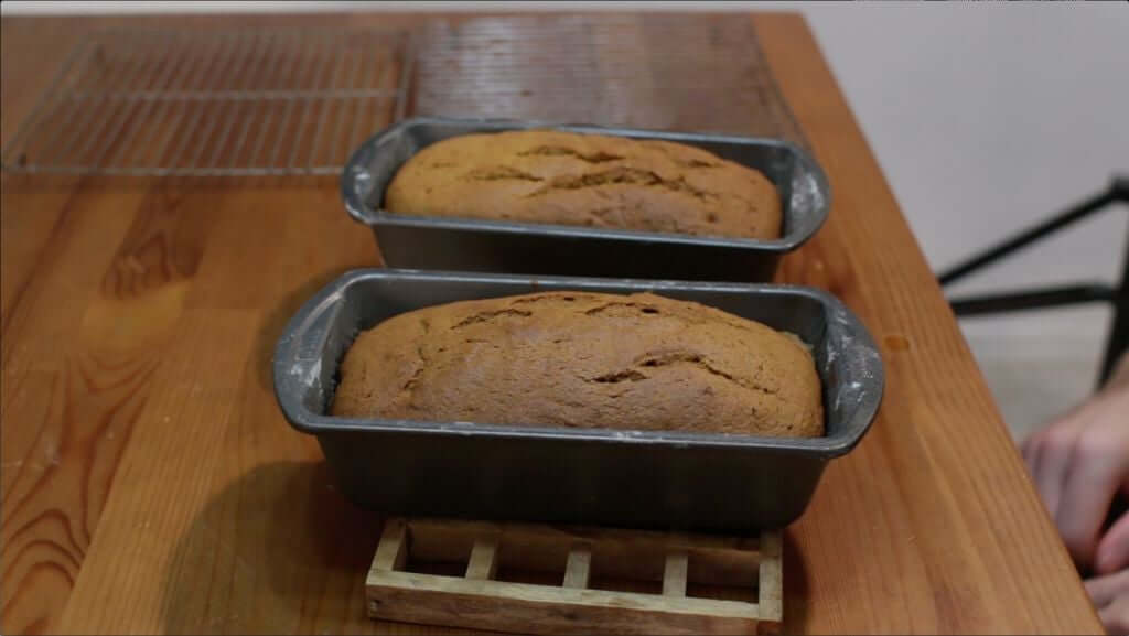 Freshly baked pumpkin bread sitting on top of a wooden table.
