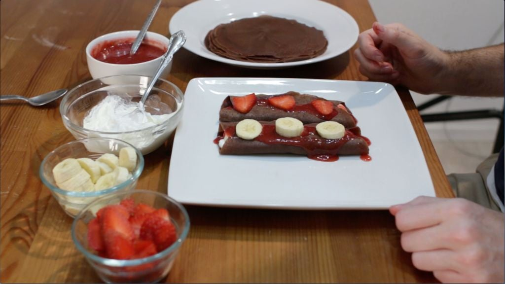 two chocolate crepes on a table with bananas and strawberries with chocolate sauce.