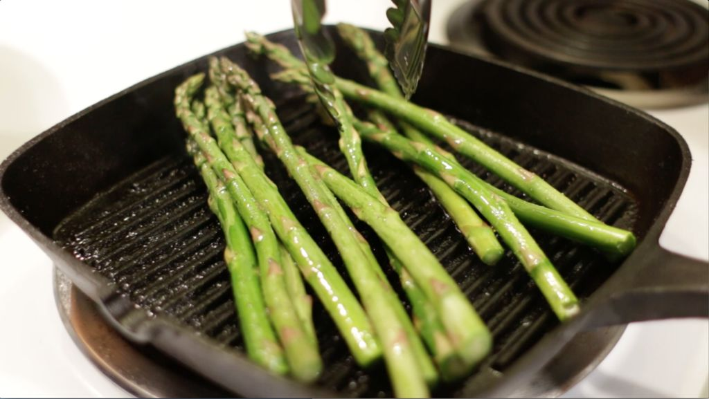 Asparagus being cooked on a cast iron grill pan.