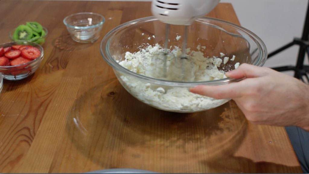White hand mixer mixing cream cheese frosting.