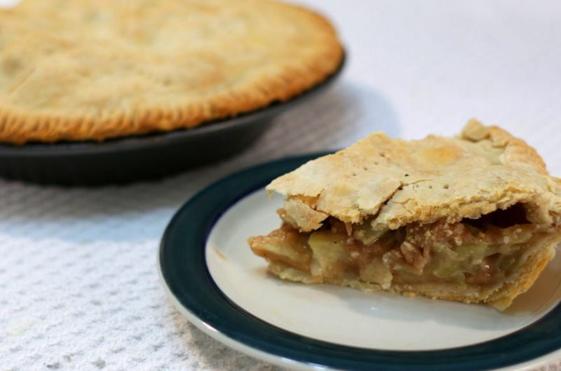 slice of easy apple pie next to another pie.