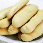 easy breadsticks piled on a white plate on a table.