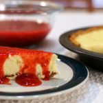 Easy cheesecake recipe with a slice of cheesecake covered in strawberry sauce on a table.