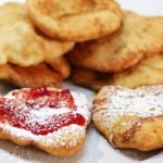 fry bread stacked on a white plate with strawberry jam and powdered sugar