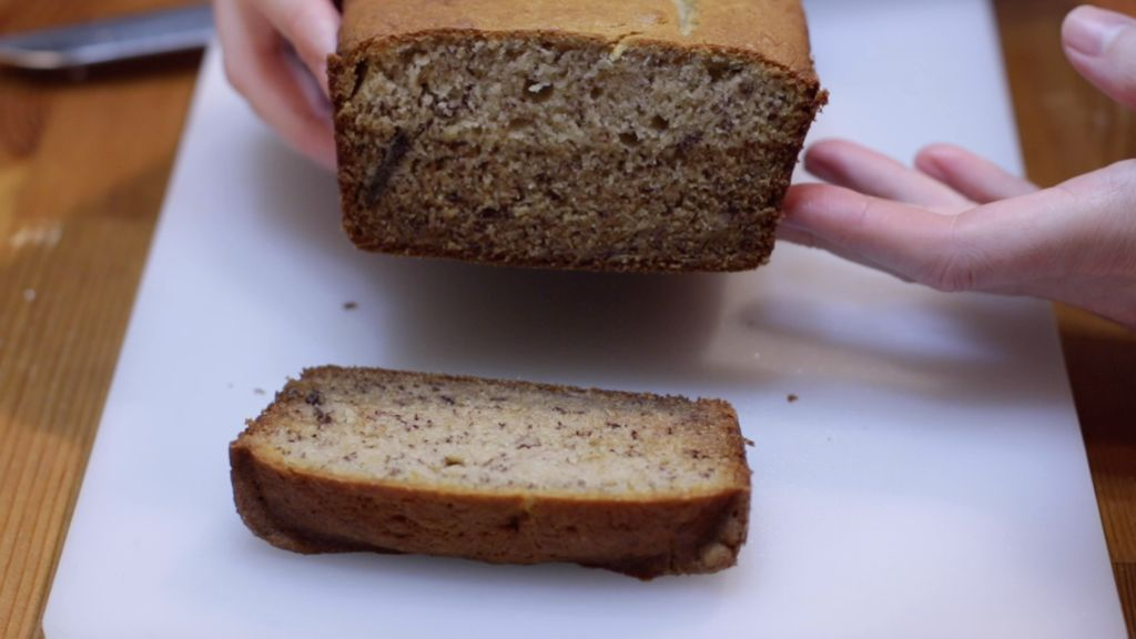 Hands holding sliced banana bread over a white cutting board.