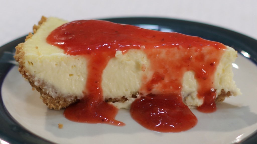 Slice of strawberry cheesecake on a plate on a table.
