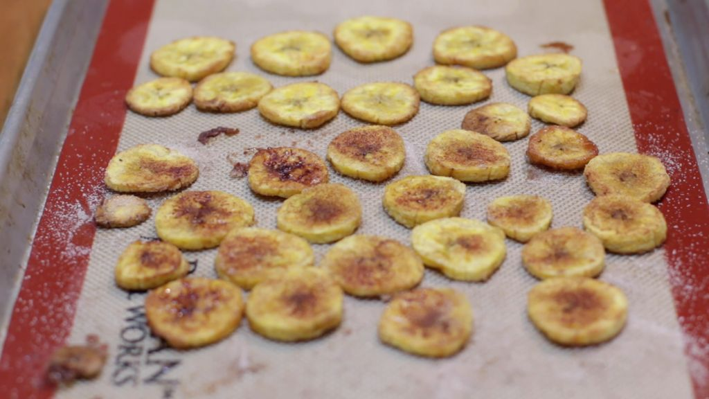 Baked plantains chips on a sheet pan lined with a silicone mat.