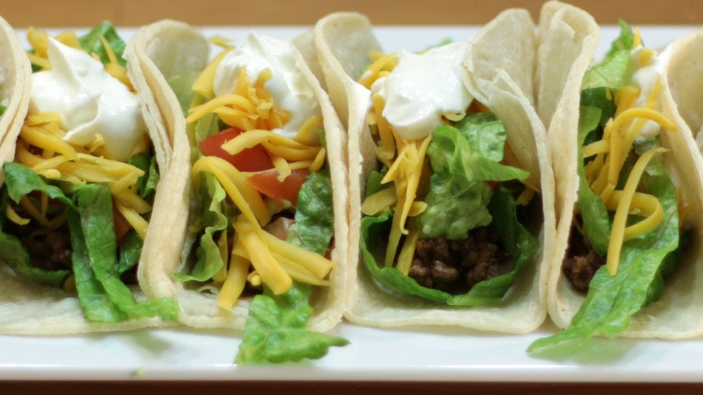 Assembled ground beef tacos on a long white plate on a wooden table.