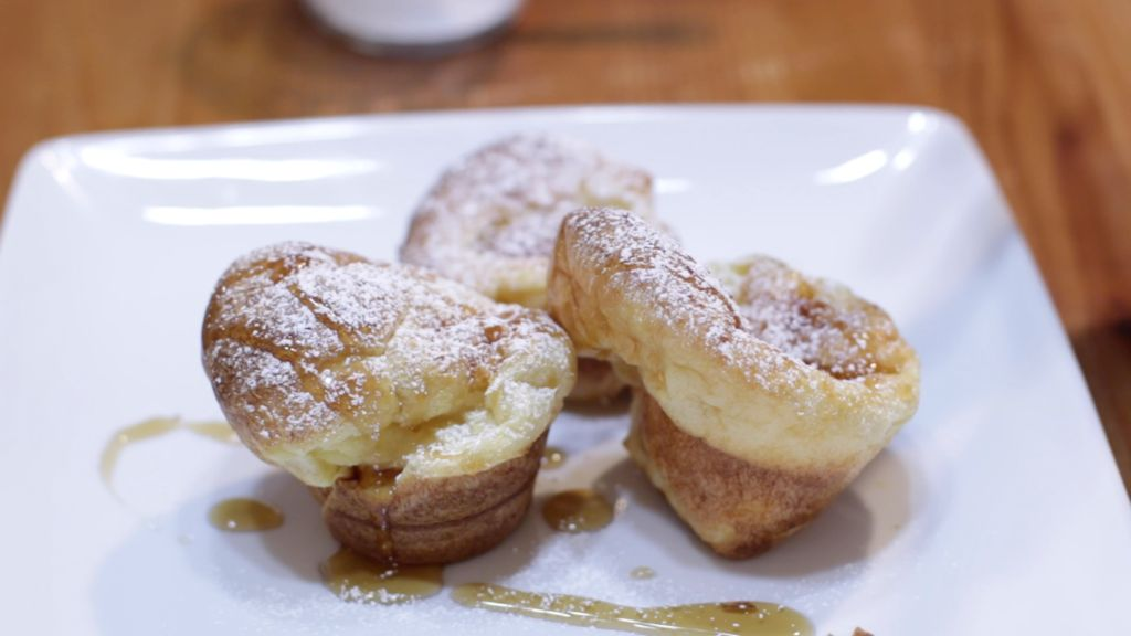 Three popovers on a white plate covered in maple syrup and powdered sugar.