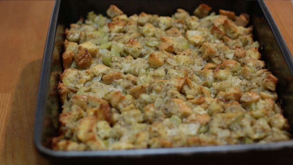 Freshly made homemade stuffing in a 13x9 metal pan on top of a wooden table.