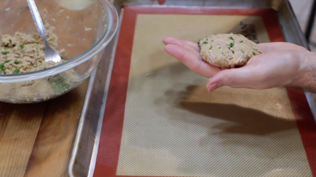 Unbaked tuna patty in a hand on top of a sheet pan lined with a silicone mat on a wooden table.