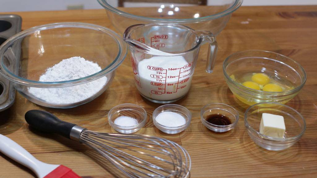 Several popover ingredients in glass bowls on a wooden table.