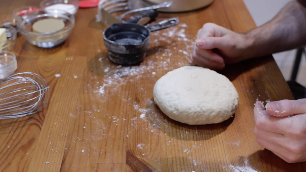Cinnamon roll dough without yeast shaped into a disc on a wooden table.