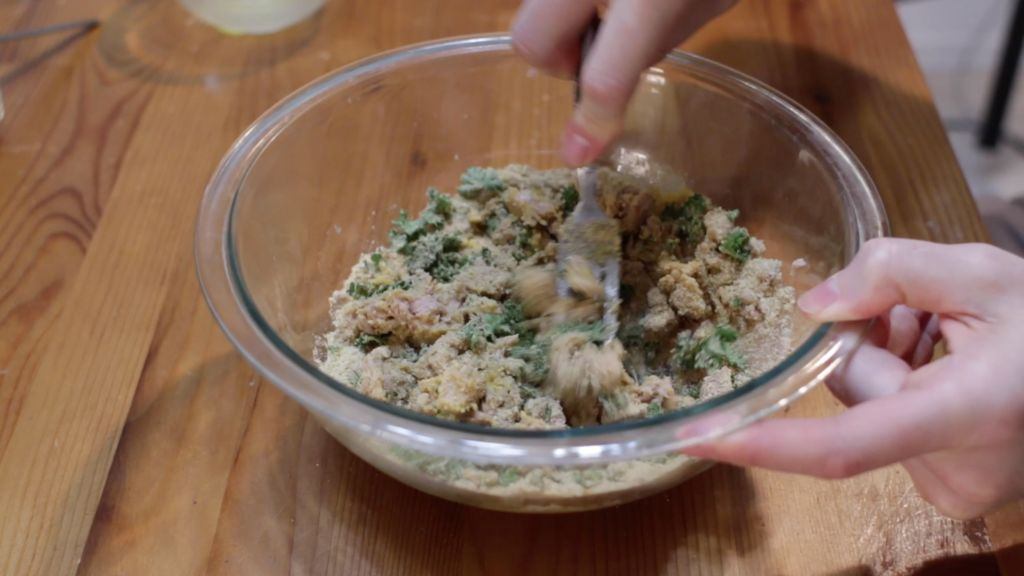 Tuna patties ingredients mixed together in a large glass bowl on a wooden table.