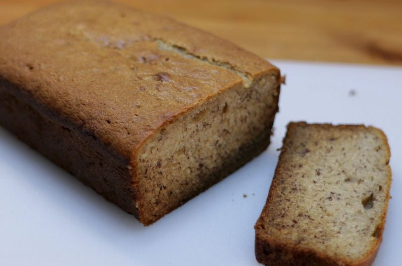 moist banana bread sliced on a white cutting board on a wooden table