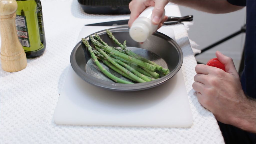 Asparagus in a pie pan with hand sprinkling on garlic powder.