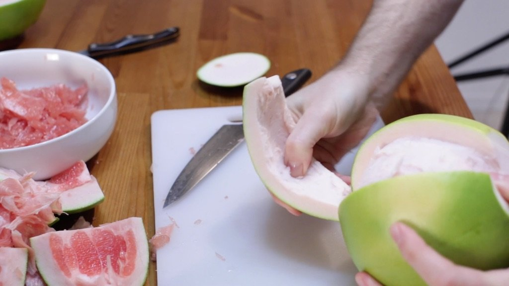 Hand peeling the thick pomelo peel away from the fruit, on a white cutting board.