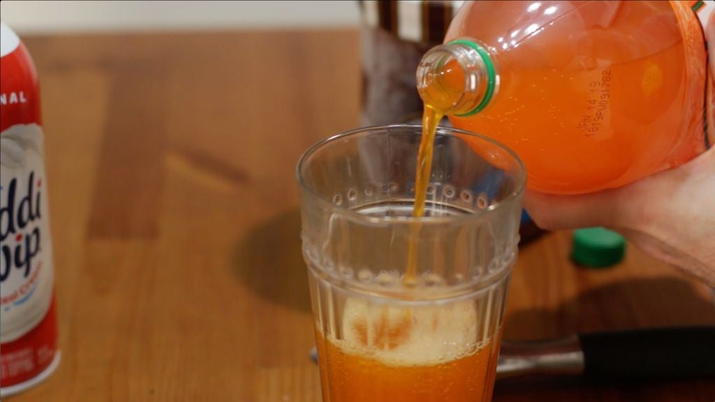 Pouring orange soda into a glass on a wooden table.
