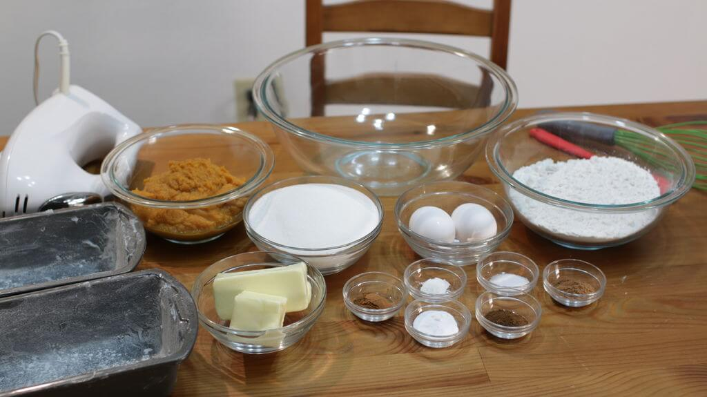 Pumpkin bread ingredients in bowls on top of a wooden table, including pure pumpkin, sugar, flour, eggs, butter, etc.