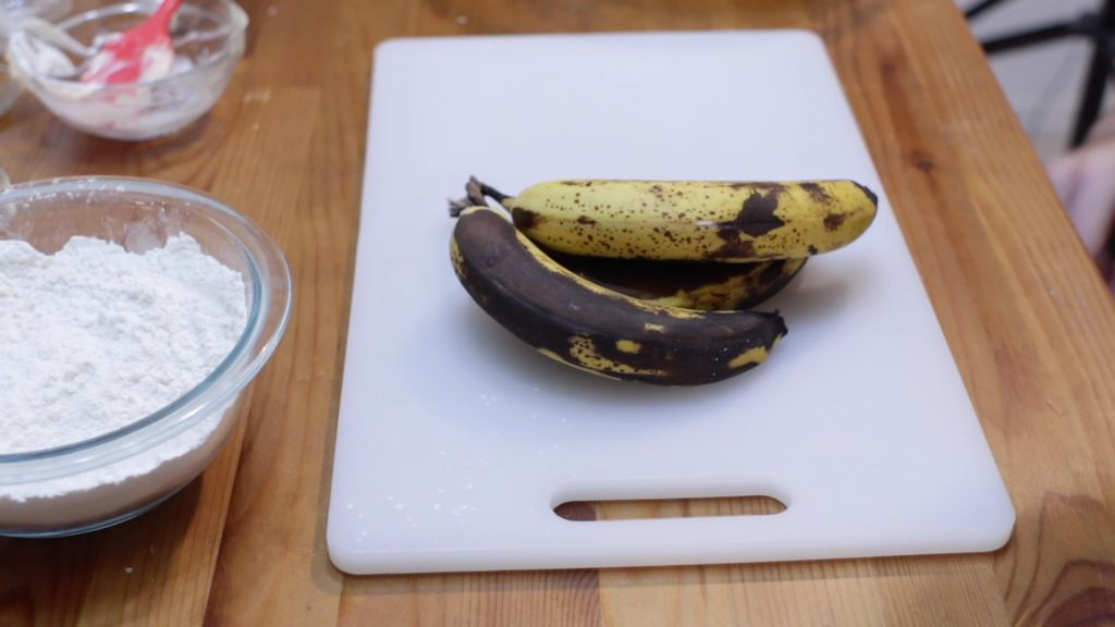 Ripe bananas on a white cutting board.