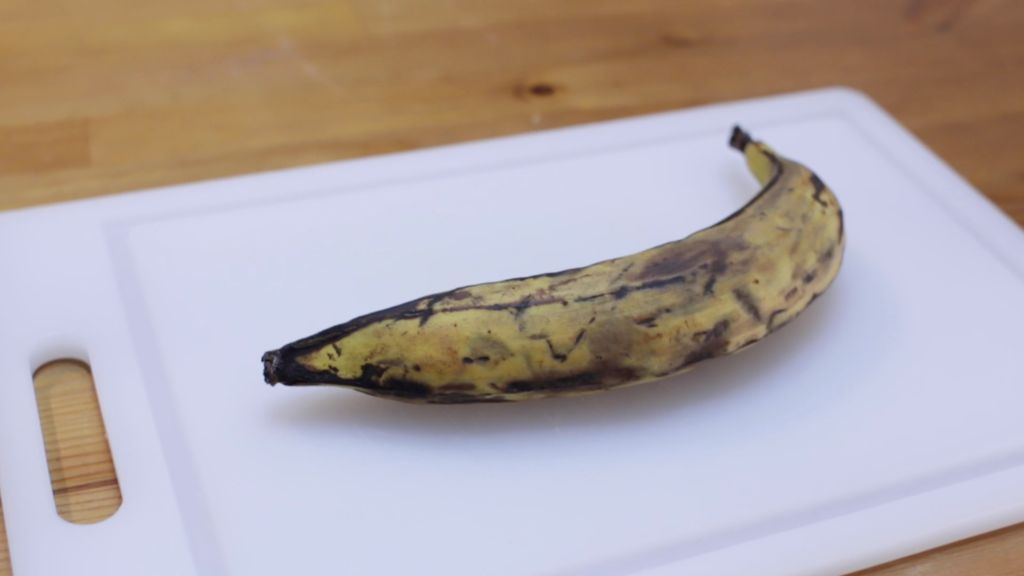 Ripe plantains on a white cutting board on a wooden table.