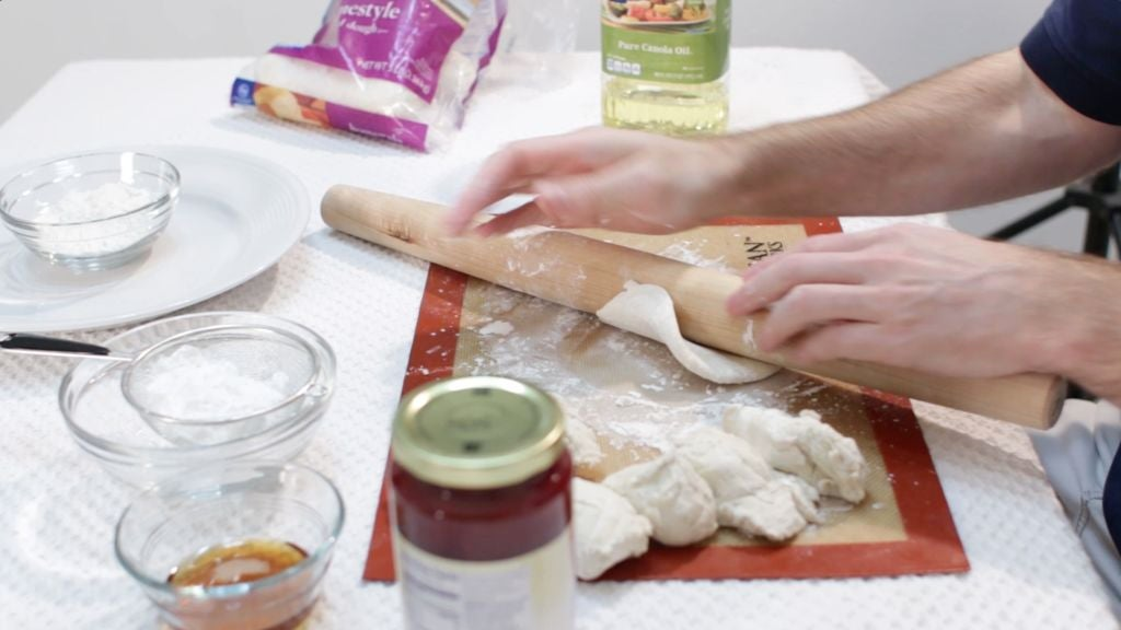 Bread dough being rolled on a floured table with a rolling pin