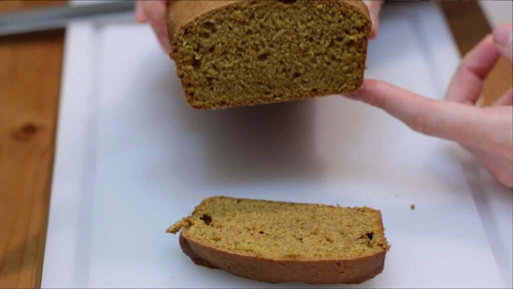 Sliced pumpkin bread being held up, over a white cutting board.