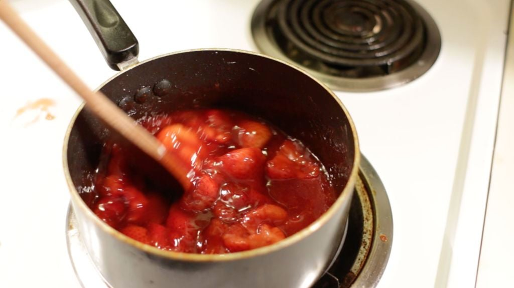 strawberry sauce in a pot on a white stovetop.