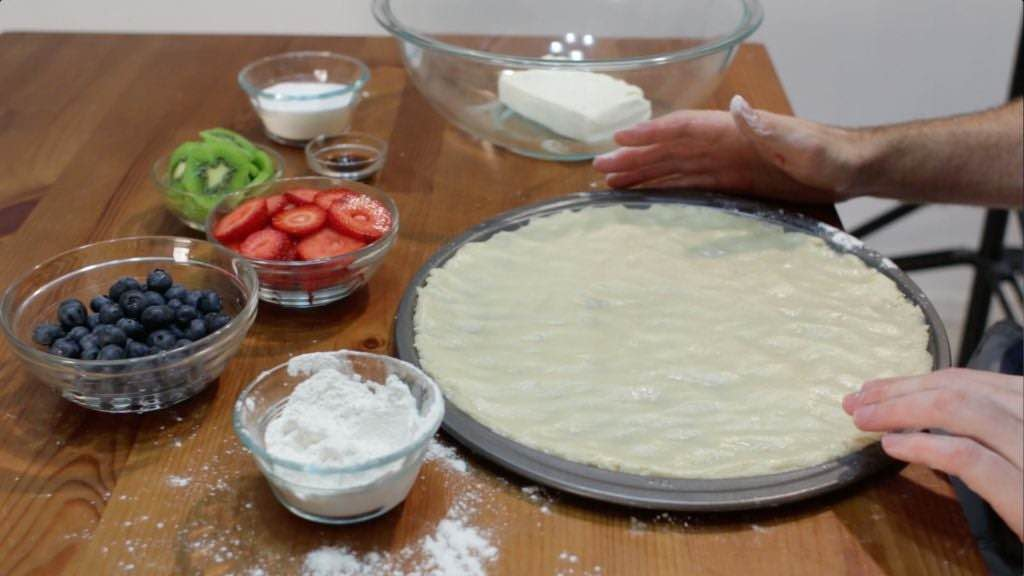 Sugar cookie crust rolled out onto a pizza pan.