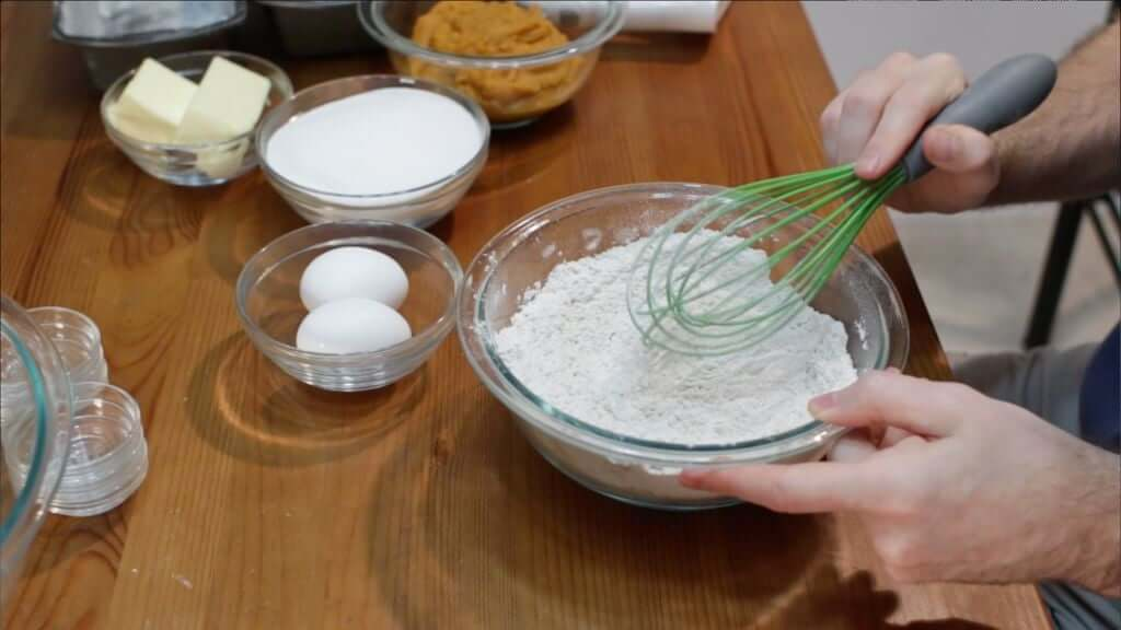 Hand whisk dry ingredients in a large glass bowl on a wooden table.
