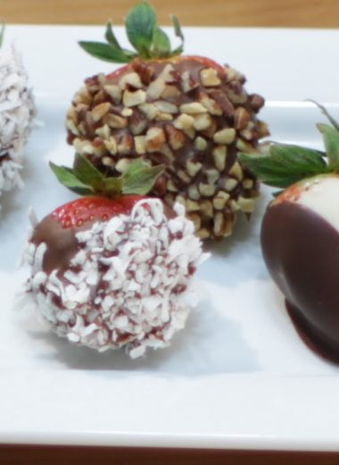 Variety of chocolate covered strawberries on a white plate
