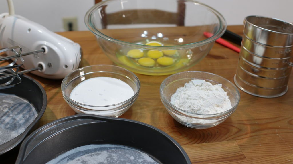 Three ingredients in bowls on a wooden table, eggs, flour, and sugar.