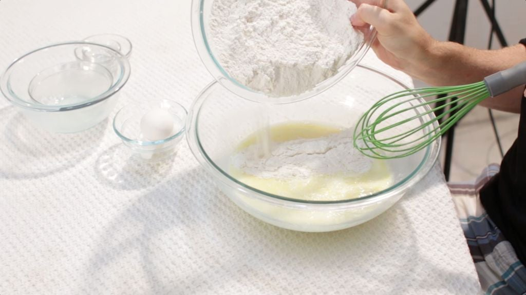 Hand pouring the dry mixture into the easy fluffy pancakes batter.