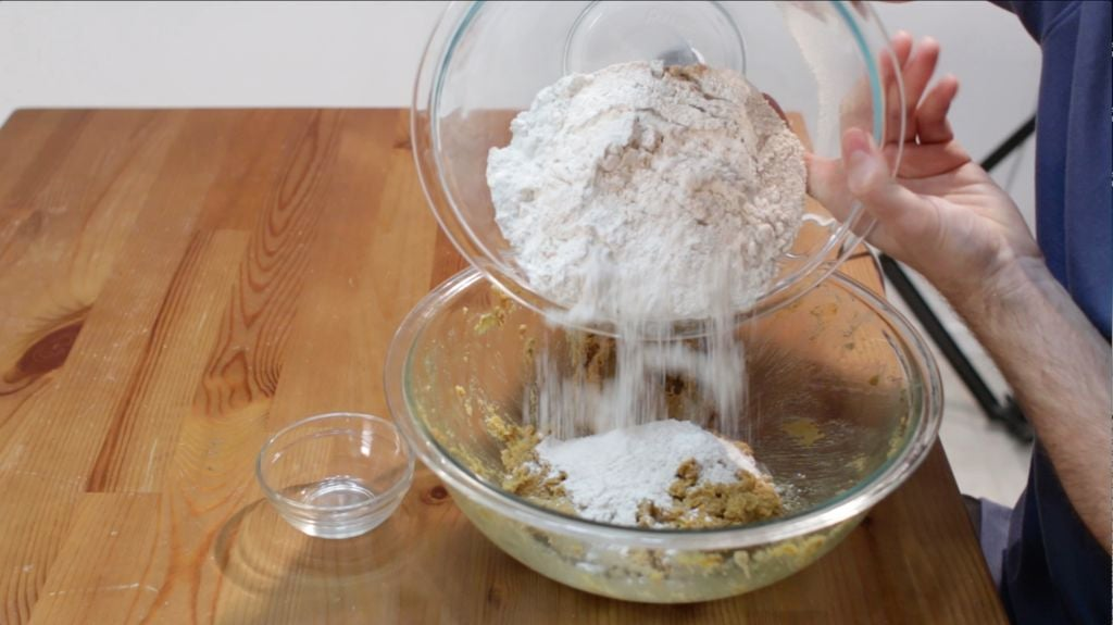 Hand with flour mixture in a bowl pouring it into a bowl with molasses cookie dough.