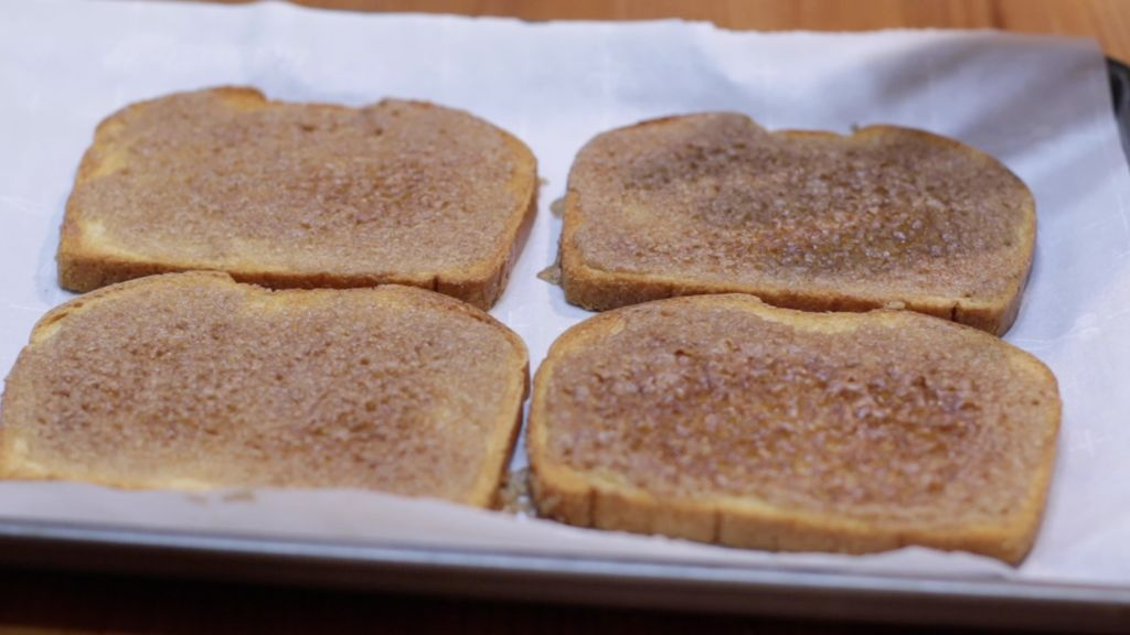 Four slices of cinnamon toast on a parchment paper-lined sheet pan.