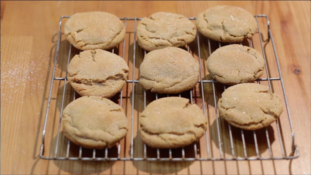 Nine homemade soft chewy molasses cookies on a wire rack on a table.