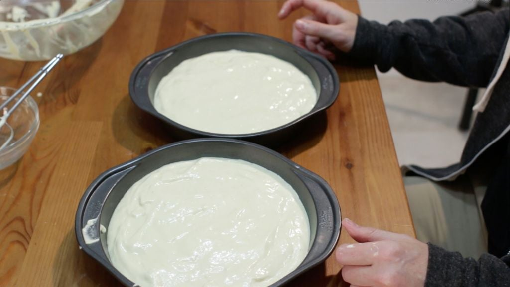 Two round pans filled with batter on a wooden table.