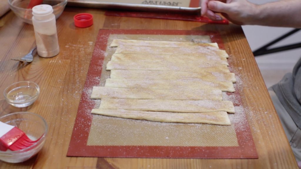 Several unbaked cinnamon twists on a silicone mat.