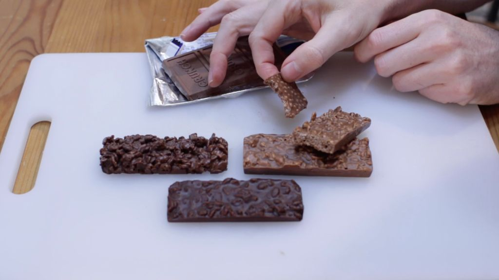 Hand holding a Nestle crunch bar with a bite out of it next to a homemade crunch bar on a white cutting board.