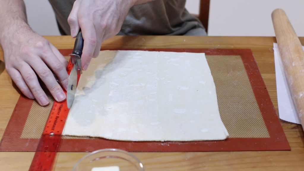 Hand with red ruler and pizza roller cutting strips out of the puff pastry.