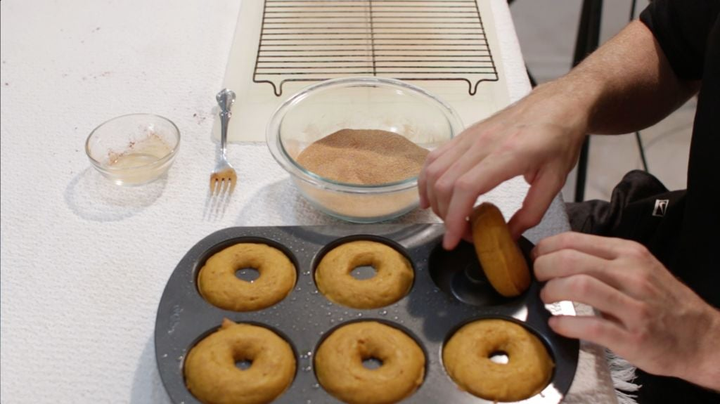 Hand removing a pumpkin donut from the doughnut pan.