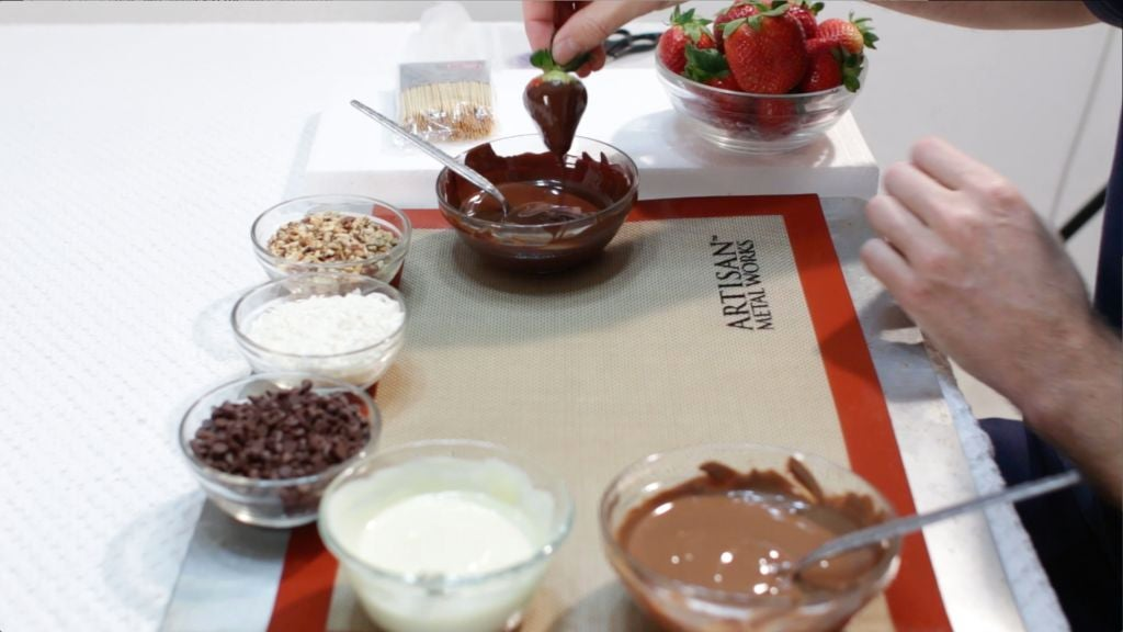 Strawberries being dipped into melted chocolate on a table.