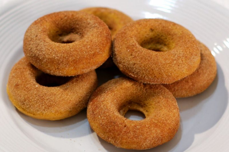 Pile of homemade pumpkin donuts on a white plate.