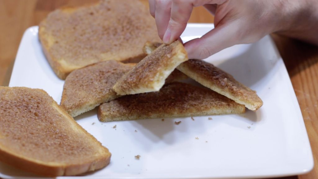 Hand holding a piece of cinnamon toast with a bite out of it over a white plate.