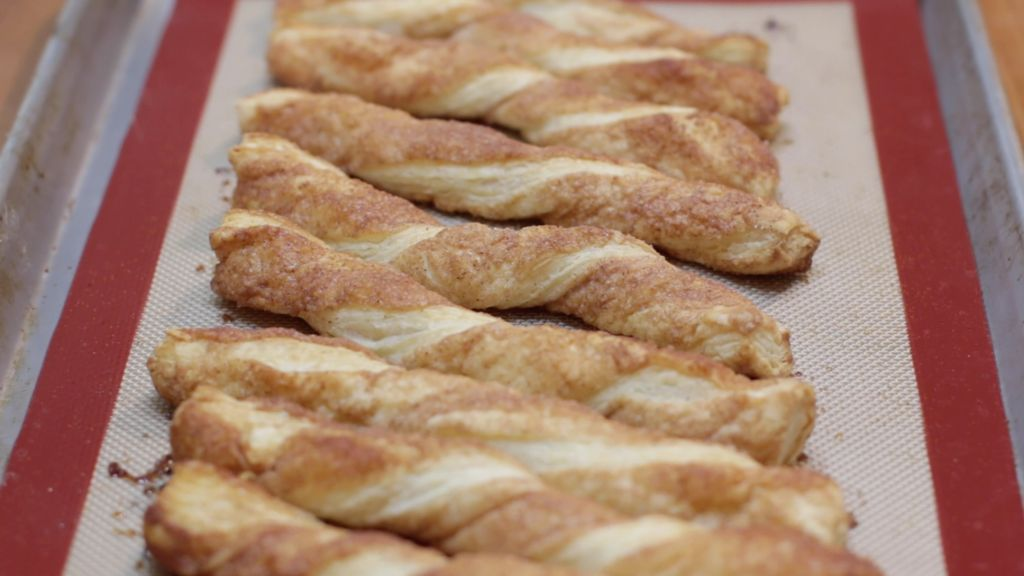 Several freshly baked cinnamon twists on a sheet pan lined with a silicone mat.