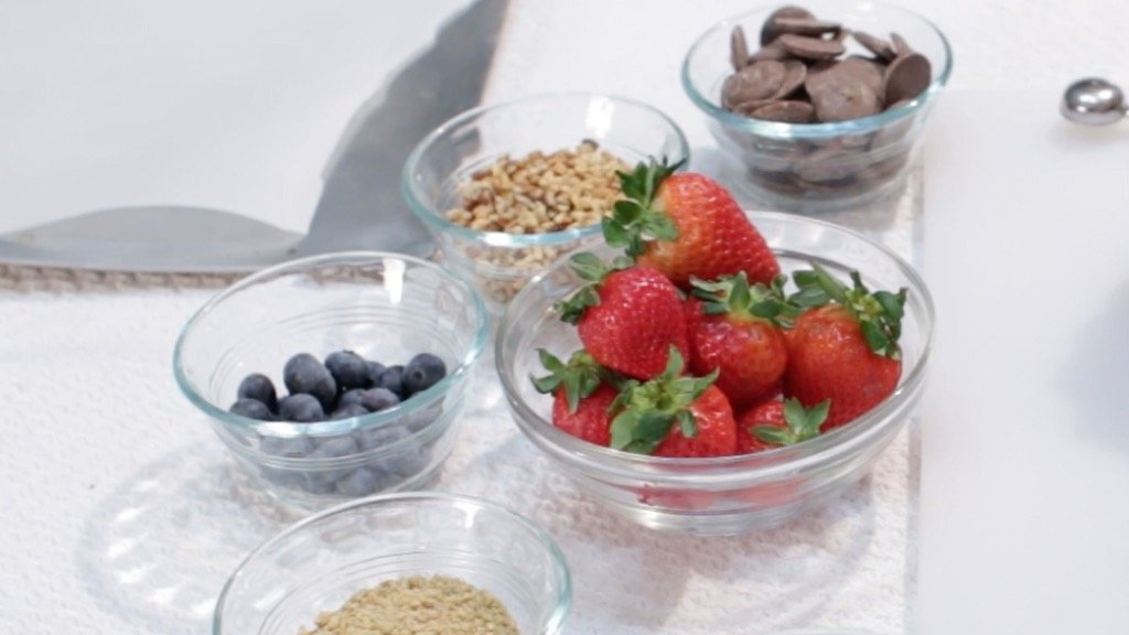 Strawberries, chocolate, and other toppings in bowls on top of a table.