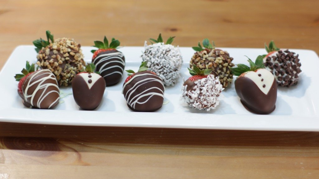 Rectangle white plate filled with several varieties of chocolate dipped strawberries.