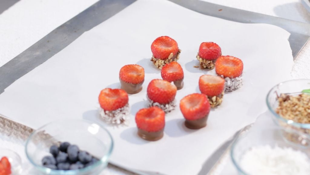 Chocolate dipped strawberries rolled in toppings on a sheet pan lined with parchment paper.